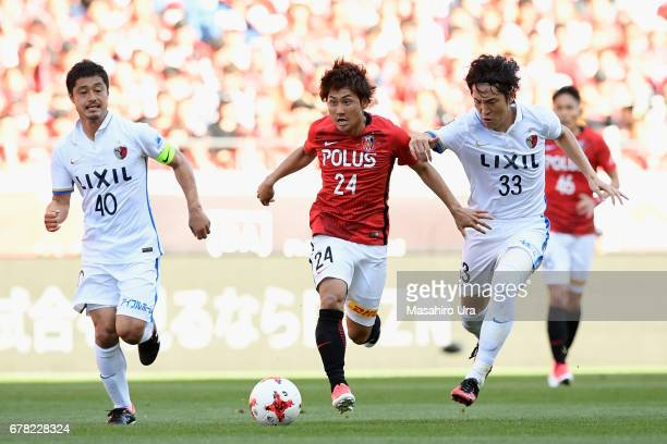Takahiro Sekine of Urawa Red Diamonds competes for the ball against Mitsuo Ogasawara and Mu Kanazaki of Kashima Antlers during the JLeague J1 match...