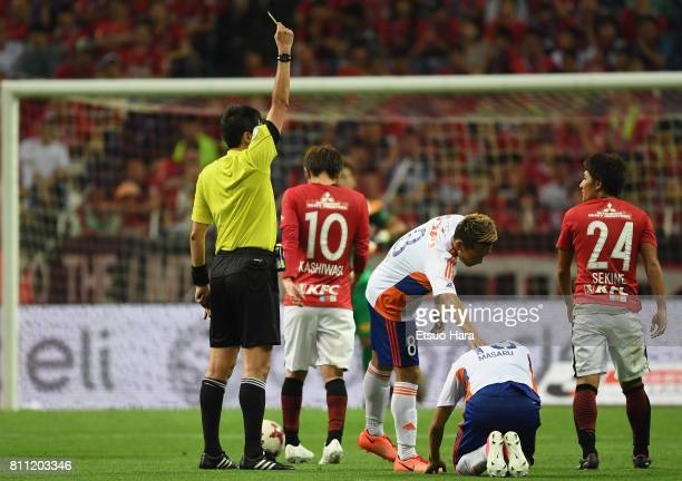 Takahiro Sekine of Urawa Red Diamonds is shown a yellow card by referee Tomohiro Inoue during the JLeague J1 match between Urawa Red Diamonds and...