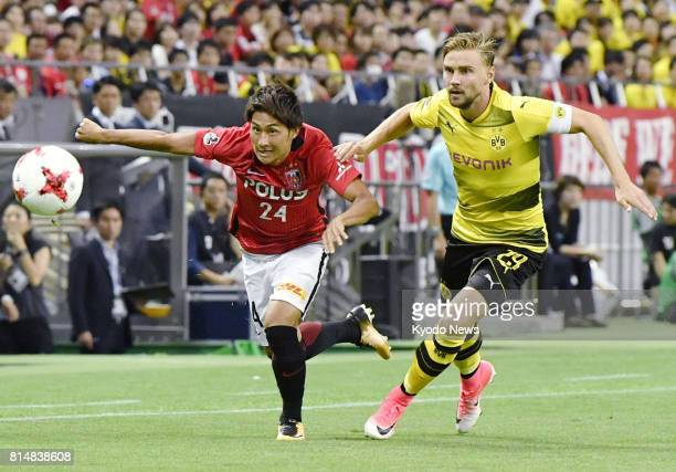 Takahiro Sekine of Urawa Reds and Marcel Schmelzer of Borussia Dortmund vie for the ball during the first half of an international friendly at...