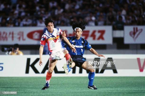Takahiro Yamada of Yokohama Marinos and Hiromitsu Isogai of Gamba Osaka compete for the ball during the J.League Suntory Series match between Gamba...