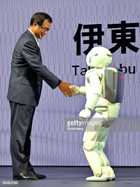 Takanobu Ito president and chief executive officer of Honda Motor Co shakes hands with the company's robot ASIMO during a news conference at the 41st...
