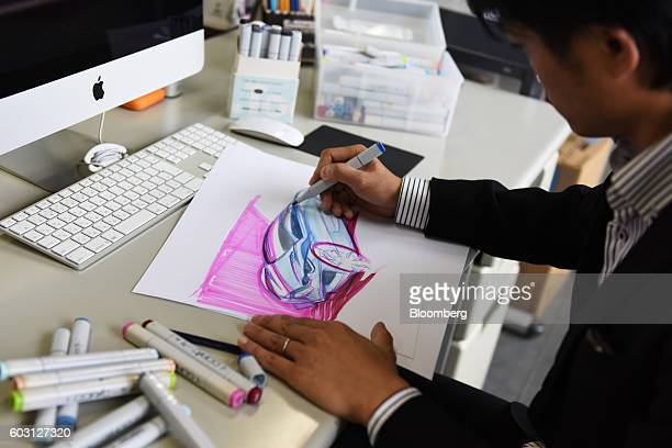 Takanori Aoki chief designer and manager of Mitsuoka Motors Co sketches ideas for a new automobile at the company's factory in Toyama Japan on...