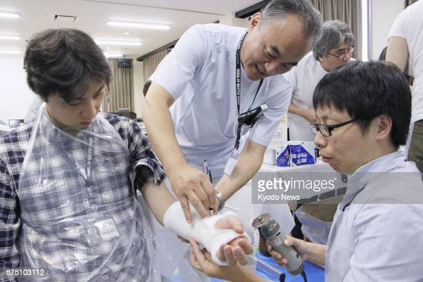 Takao Inoue a 55yearold orthopedics doctor running a clinic in Masuda city Shimane Prefecture teaches how to apply a plaster cast to a patient A...