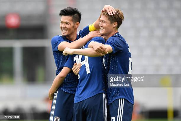 Takashi Inui of Japan celebrates scoring his side's second goal with his team mates Gotoku Sakai and Hotaru Yamaguchi during the international...