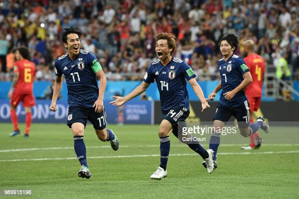 Takashi Inui of Japan celebrates with team mates Makoto Hasebe and Gaku Shibasaki after scoring his team's second goal during the 2018 FIFA World Cup...