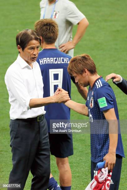 Takashi Inui of Japan is consoled by head coach Akira Nishino after their 23 defeat in the 2018 FIFA World Cup Russia Round of 16 match between...