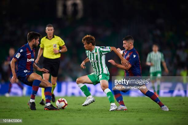 Takashi Inui of Real Betis Balompie being followed by Enis Bardhi of Levante UD and Prcic of Levante UD during the La Liga match between Real Betis...