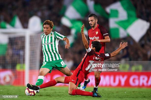 Takashi Inui of Real Betis Balompie competes for the ball with Jesus Navas of Sevilla FC during the La Liga match between Real Betis Balompie and...
