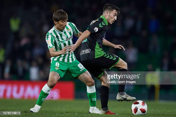Takashi Inui of Real Betis competes for the ball with Aitor Buñuel of Racing de Santander during the Spanish Copa del Rey second Leg match between...