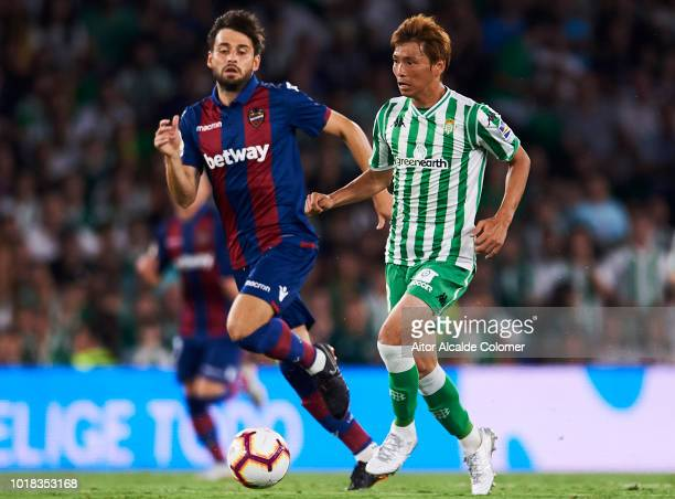 Takashi Inui of Real Betis competes for the ball with Sanjin Prcic of Levante UD during the La Liga match between Real Betis Balompie and Levante UD...