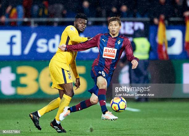 Takashi Inui of SD Eibar duels for the ball with Thomas Teye Partey of Atletico Madrid during the La Liga match between SD Eibar and Atletico Madrid...