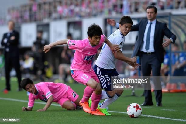 Takashi Kanai of Yokohama F.Marinos and Yuzo Kobayashi of Sagan Tosu compete for the ball during the J.League J1 match between Sagan Tosu and...