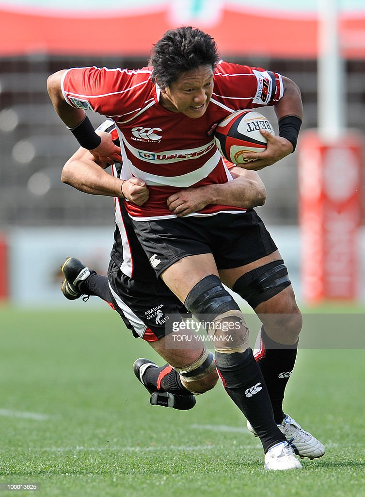 Takashi Kikutani (facing) of Japan holds onto the ball as he is tackled by Jonathan MacDonald (behind) of the Arabian Gulf team during their match in the Asian Five Nations rugby tournament in Tokyo on May 8, 2010. Japan defeated Arabian Gulf 60-5. AFP PHOTO/Toru YAMANAKA