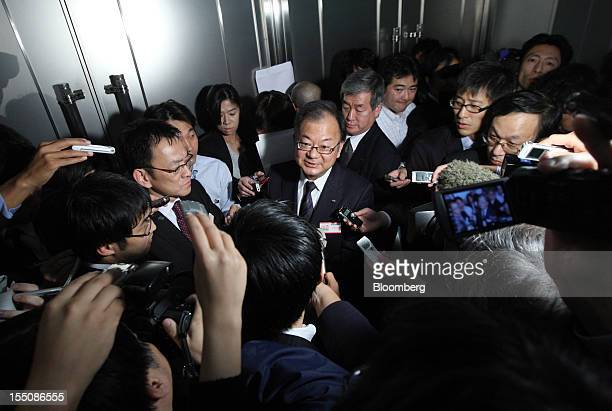 Takashi Okuda president of Sharp Corp center is surrounded by the media after a news conference in Tokyo Japan on Thursday Nov 1 2012 Sharp the...