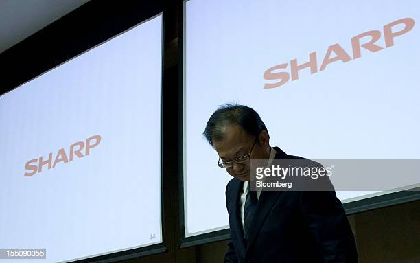 Takashi Okuda president of Sharp Corp walks past the company's logo displayed during a news conference in Tokyo Japan on Thursday Nov 1 2012 Sharp...