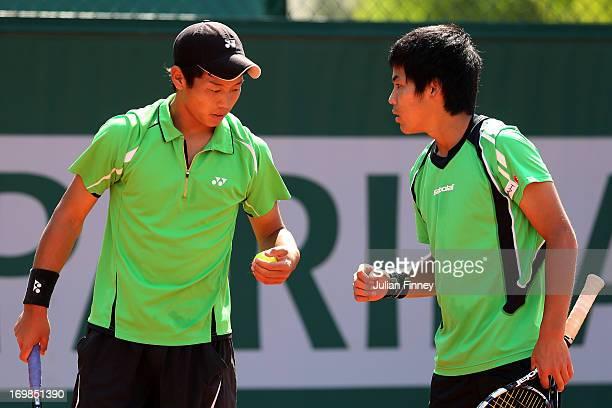 Takashi Saito and Ken Onishi of Japan talk tactics during their boys' doubles match between Takashi Saito and Ken Onishi of Japan and Maxime Hamou...