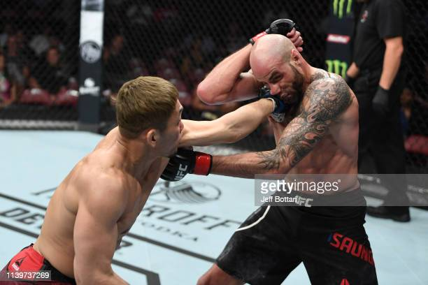 Takashi Sato of Japan punches Ben Saunders in their welterweight bout during the UFC Fight Night event at BB&T Center on April 27, 2019 in Sunrise,...