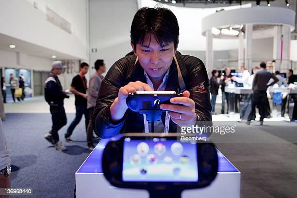 Takashi Sato Sony tests out the Sony Computer Entertainment Inc. PlayStation Vita portable video game player at the 2012 International Consumer...