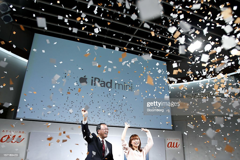 Takashi Tanaka, president of KDDI Corp., left, and actress Satomi Shigemori cheer during the launch of the Apple Inc. iPad Mini at a KDDI store in Tokyo, Japan, on Friday, Nov. 30, 2012. The iPad Mini went on sale at KDDI and Softbank Corp. stores in Japan today. Photographer: Kiyoshi Ota/Bloomberg via Getty Images