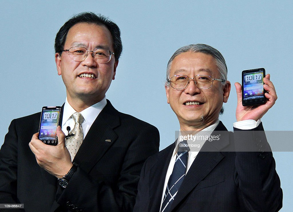 Takashi Tanaka, president of KDDI Corp., left, and Fred Liu, vice president of HTC corp., hold up htc EVO WiMAX smartphones manufactured by HTC corp., during an unveiling in Tokyo, Japan, on Monday, Feb. 28, 2011. KDDI is Japan's second-largest mobile-phone operator. Photographer: Haruyoshi Yamaguchi/Bloomberg via Getty Images