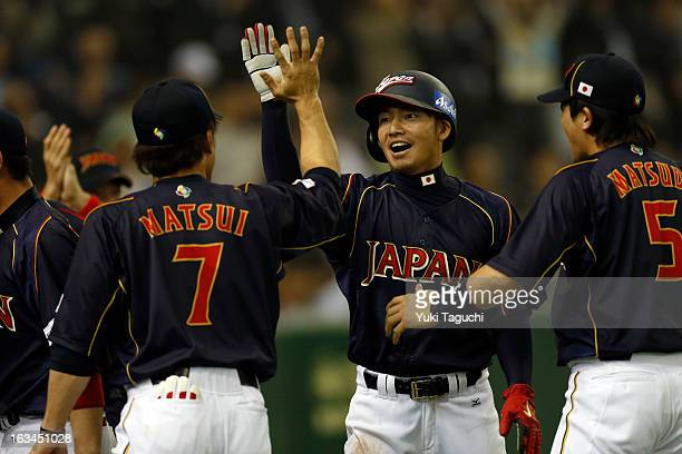 Takashi Toritani of Team Japan is greeted by teammates after scoring the game tying run in the top of the ninth inning during Pool 1 Game 2 between...