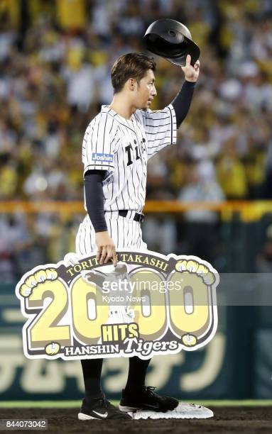 Takashi Toritani of the Hanshin Tigers acknowledges the crowd after picking up his 2000th career hit in the second inning against the DeNA BayStars...