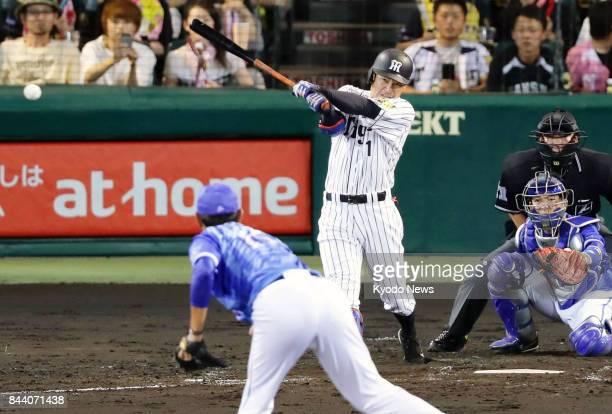 Takashi Toritani of the Hanshin Tigers hits an RBI double in the second inning against the DeNA BayStars at Koshien Stadium in Nishinomiya Japan on...