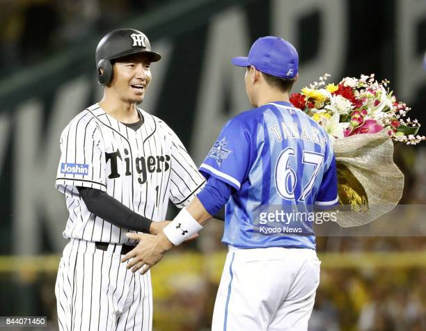 Takashi Toritani of the Hanshin Tigers receives flowers from Hiroyasu Tanaka of the DeNA BayStars after picking up his 2000th career hit in the...