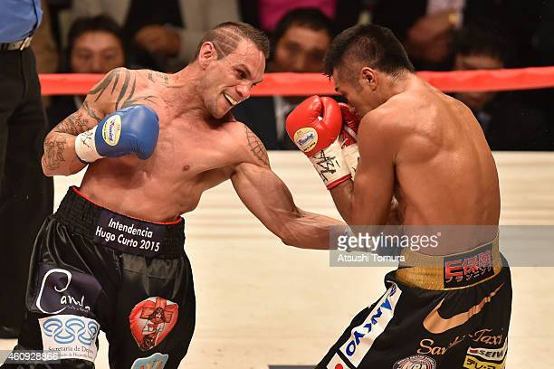 Takashi Uchiyama of Japan and Israel Hector Enrique Perez of Argentina exchange punches during the WBA world super featherweight bout between Takashi...