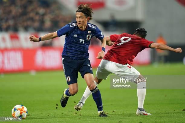 Takashi Usami of Japan in action against Rodrigo Ramallo of Bolivia during the international friendly match between Japan and Bolivia at Noevir...