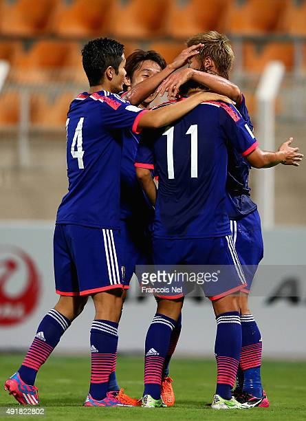 Takashi Usami celebrates with teammates after scoring his team's third goal during the 2018 FIFA World Cup Asian Group E qualifying match between...