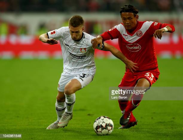Takashi Usami of Duesseldorf and Mitchell Weiser of Leverkusen battle for the ball during the Bundesliga match between Fortuna Duesseldorf and Bayer...
