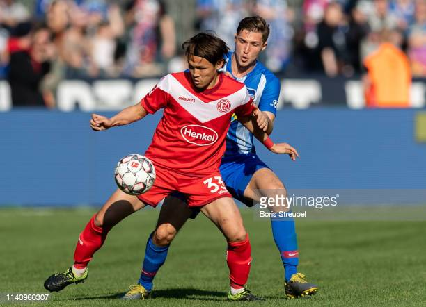 Takashi Usami of Fortuna Duesseldorf is challenged by Niklas Stark of Hertha BSC during the Bundesliga match between Hertha BSC and Fortuna...
