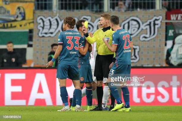 Takashi Usami of Fortuna Duesseldorf receives a yellow card during the Bundesliga match between FC Augsburg and Fortuna Duesseldorf at WWKArena on...