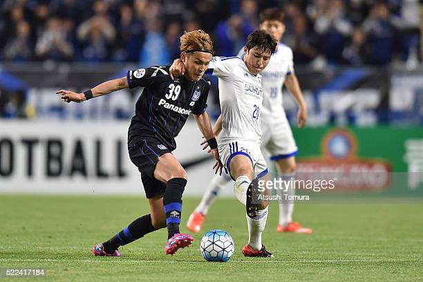 Takashi Usami of Gamba Osaka and Baek JiHoon of Suwon Samsung Bluewings FC compete for the ball during the AFC Champions League Group G match between...