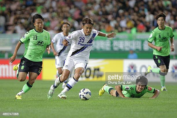 Takashi Usami of Gamba Osaka compete for the ball with Jung Hoon of Jeonbuk Hyundai Motors during the AFC Champions League quarter final match...