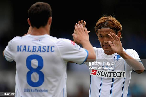 Takashi Usami of Hoffenheim celebrates with teammate Filip Malbasic after scoring his team's third goal during the friendly match between FC-Astoria...