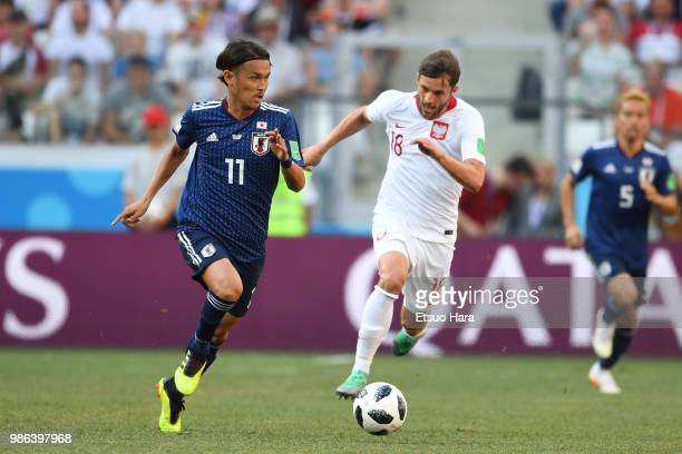 Takashi Usami of Japan and Bartosz Bereszynski of Poland compete for the ball during the 2018 FIFA World Cup Russia group H match between Japan and...