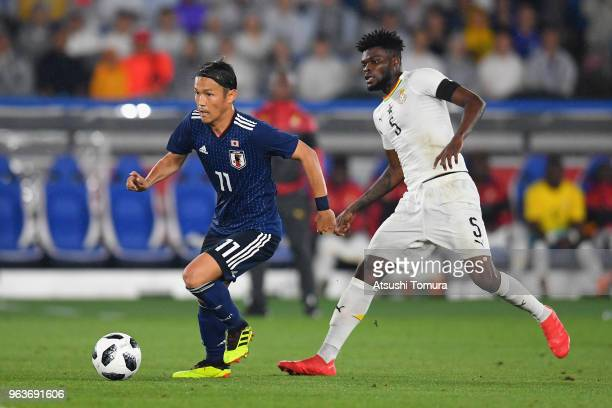 Takashi Usami of Japan and Thomas Partey of Ghana compete for the ball during the international friendly match between Japan and Ghana at Nissan...