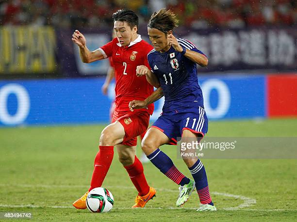 Takashi Usami of Japan battles for the ball against Ren Hang of China during the EAFF East Asian Cup 2015 final round at the Wuhan Sports Center...