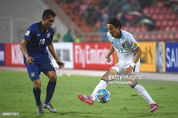 Takashi Usami of Japan competes for the ball against Teerasil Dangda of Thailand during the 2018 FIFA World Cup Qualifier between Thailand and Japan...