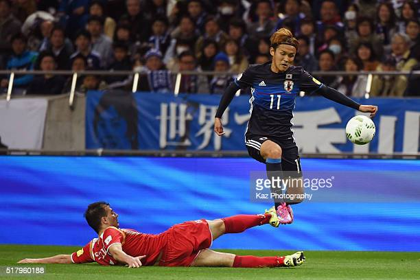 Takashi Usami of Japan is tackled during the FIFA World Cup Russia Asian Qualifier second round match between Japan and Syria at the Saitama Stadium...