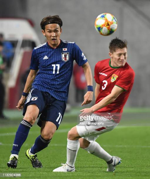 Takashi Usami of Japan passes the ball under the challenge from Alejandro Chumacero of Bolivia during the international friendly match between Japan...