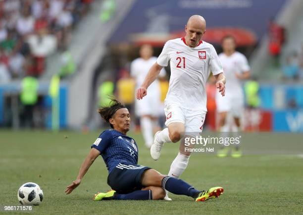 Takashi Usami of Japan tackles Rafal Kurzawa of Poland during the 2018 FIFA World Cup Russia group H match between Japan and Poland at Volgograd...