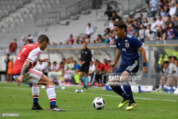 Takashi Usami of Japan takes on Alan Benitez of Paraguay during the international friendly match between Japan and Paraguay at Tivoli Stadion on June...