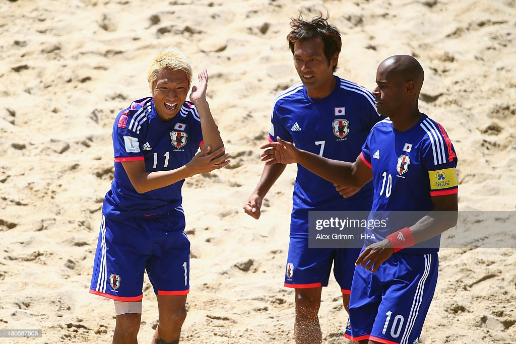 Takasuke Goto of Japan celebrates his team's first goal with team mates Teruki Tabata and Ozu Moreira (L-R) during the FIFA Beach Soccer World Cup Portugal 2015 Group A match beween Japan and Senegal at Espinho Stadium on July 13, 2015 in Espinho, Portugal.