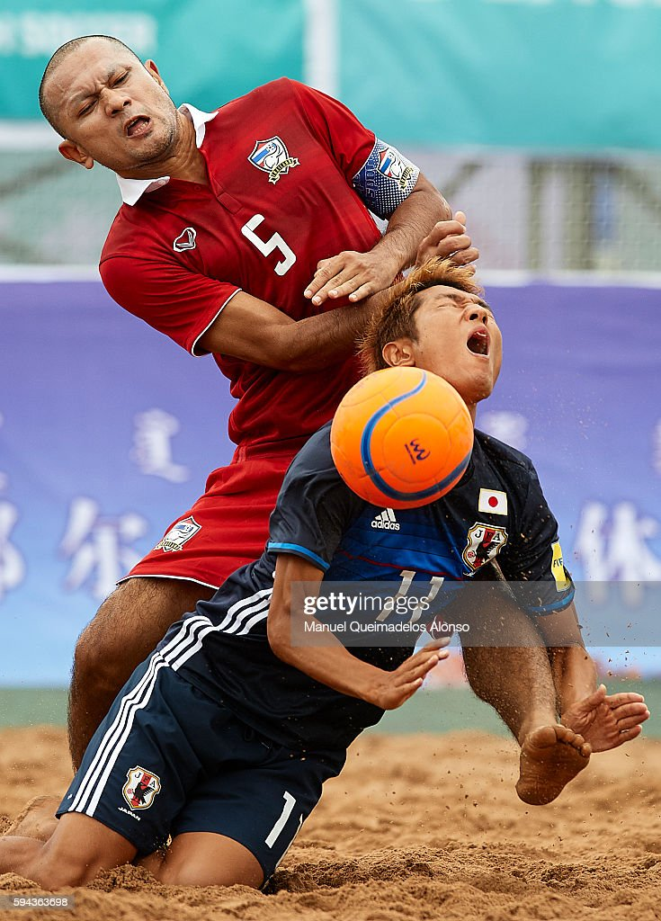 Takasuke Goto (R) of Japan is tackled by Pongsak Khongkaew of Thailand during the Continental Beach Soccer Tournament match between Japan and Thailand at Municipal Sports Center on August 23, 2016 in Ordos of Inner Mongolia Autonomous Region, China.