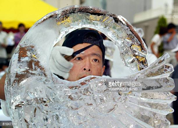 Takayuki Igarashi makes a swan sculpture from a 100kg ice cube during the annual ice sculpture contest in Tokyo 11 July 2004 one hundred contestants...