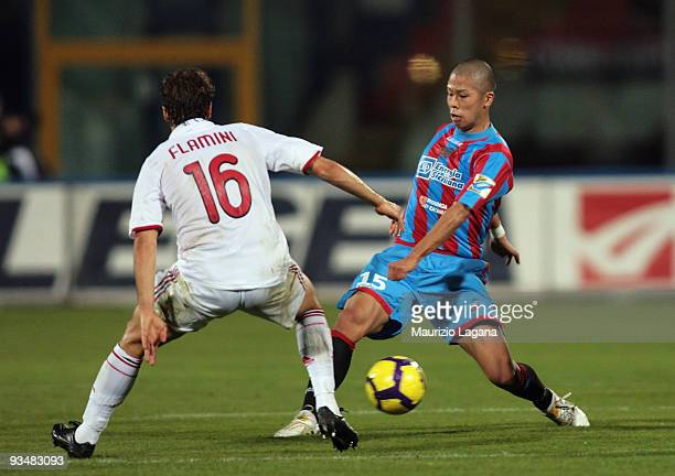 Takayuki Morimoto of Catania Calcio battles for the ball with Mathieu Flamini of AC Milan during the Serie A match between Catania Calcio and AC...