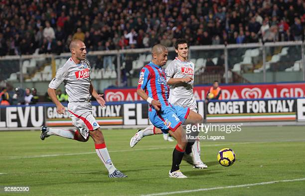 Takayuki Morimoto of Catania Calcio is challeged by Paolo Cannavaro of SSC Napoli during the Serie A match between Catania Calcio and SSC Napoli at...